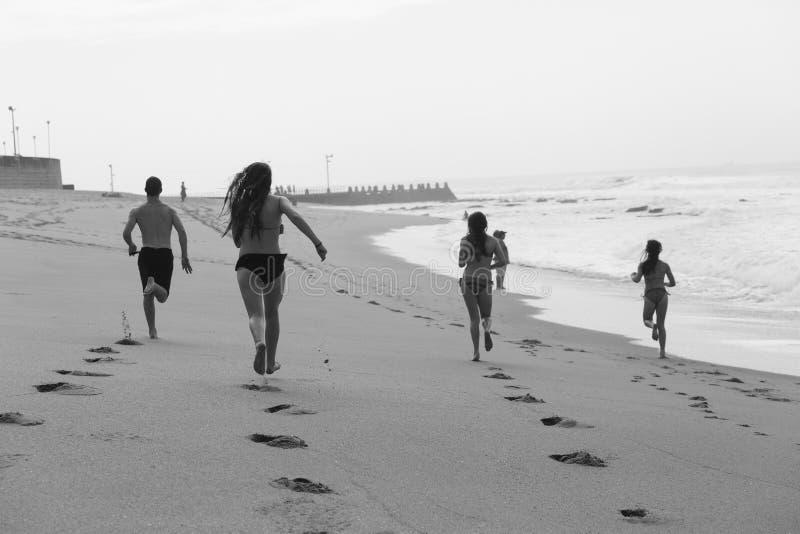 Белизна черноты пляжа мальчика девушек идущая стоковые изображения rf