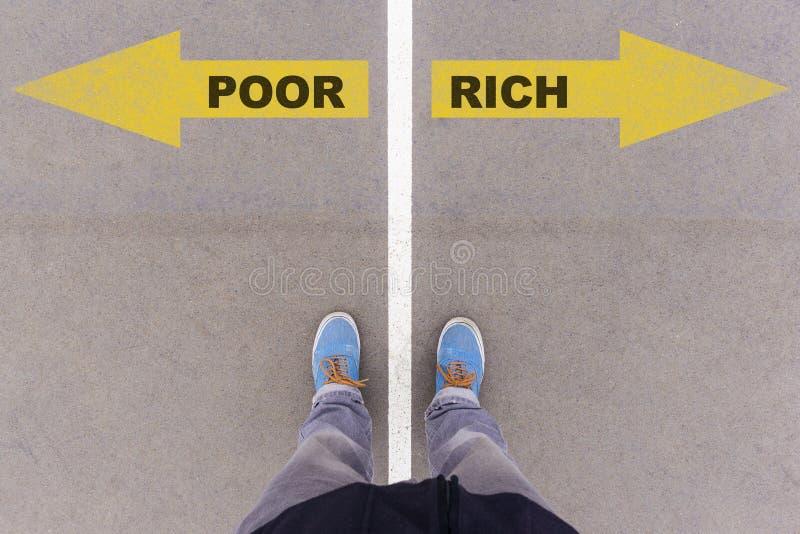 Бедные против богатых стрелок текста на земле, ногах и ботинках асфальта на fl стоковое изображение