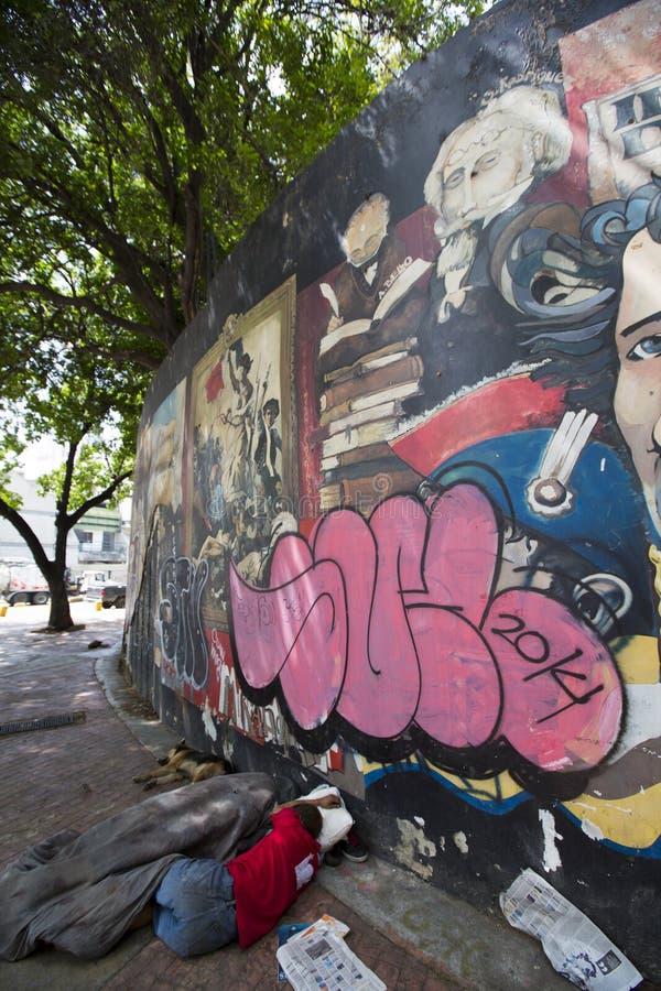 Бедный человек спать на поле с граффити Симон Боливар, Cara стоковые фотографии rf