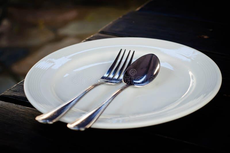Белое блюдо с ложкой и вилкой стоковое фото rf