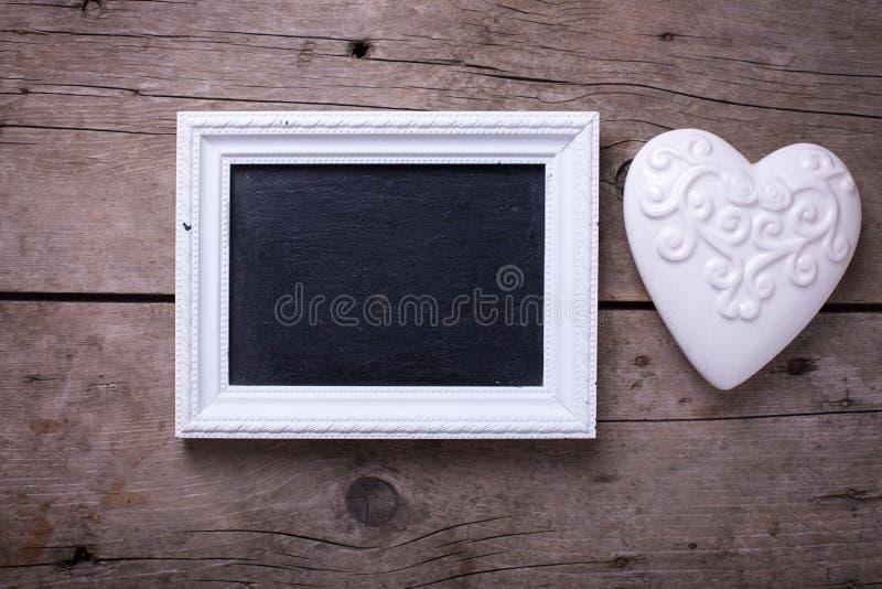 Белое декоративное сердце и пустое классн классный на деревенском деревянном ба стоковые фото
