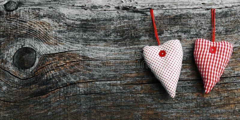 2 белое и красные материальные сердца на темной деревянной предпосылке стоковое фото