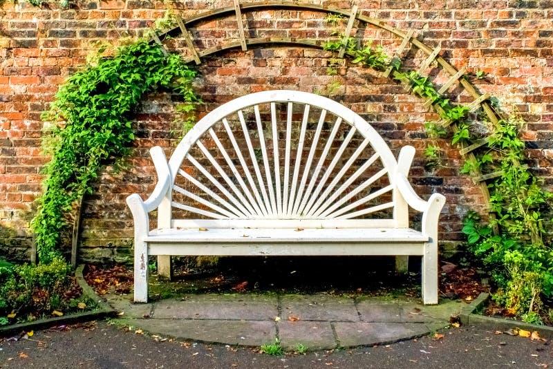 Белое место скамейки в парке против старой кирпичной стены стоковое изображение rf