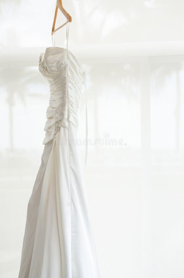 Белое платье свадьбы держа в комнате стоковая фотография