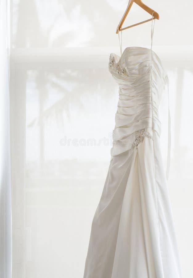 Белое платье свадьбы держа около окна стоковое изображение rf