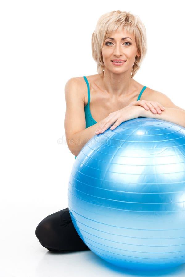 Белокурая дама сидя за шариком фитнеса стоковые изображения