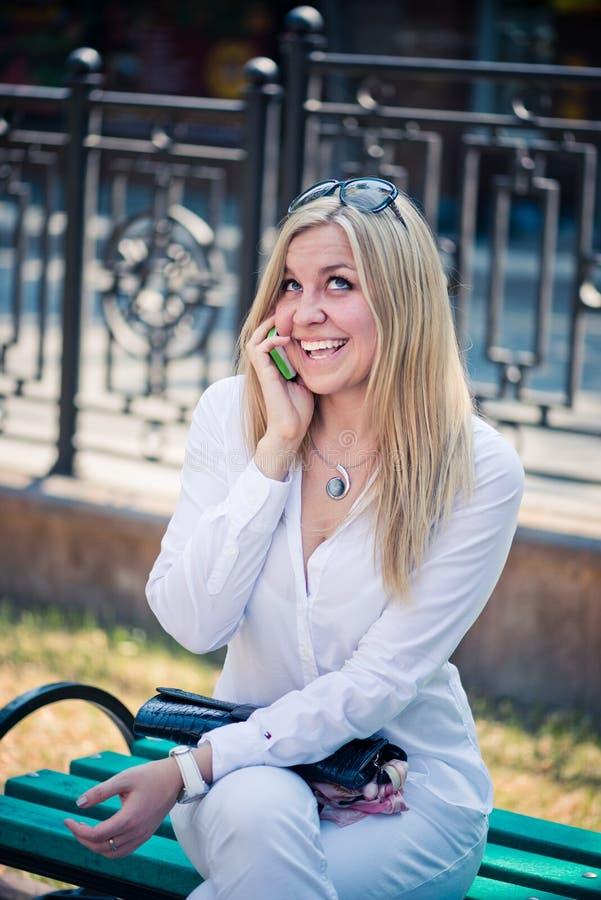 Белокурая беседа женщины телефоном внешним стоковая фотография