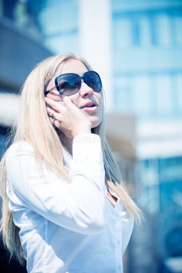 Белокурая беседа женщины телефоном внешним стоковые изображения rf