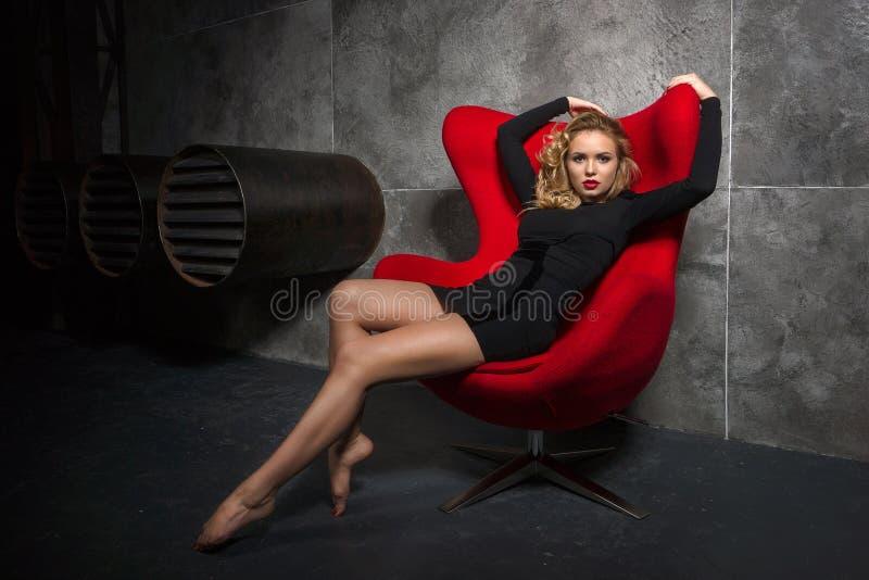 Белокурая девушка в черном платье сидя на красном кресле стоковое изображение rf