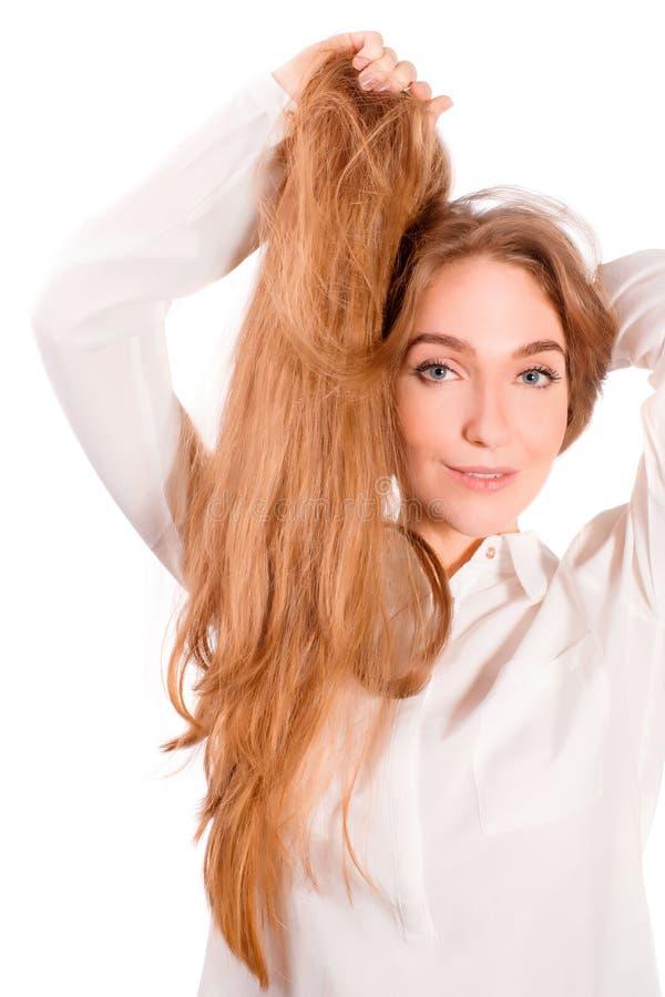 Белокурая девушка держа ее красивые волосы стоковые фото