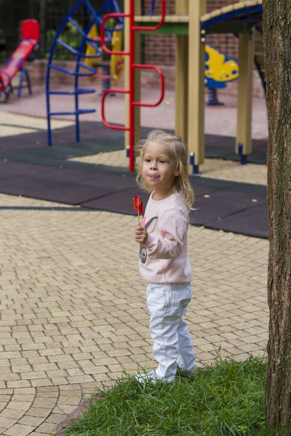 Белокурая девушка есть часть конфеты в парке стоковое изображение rf