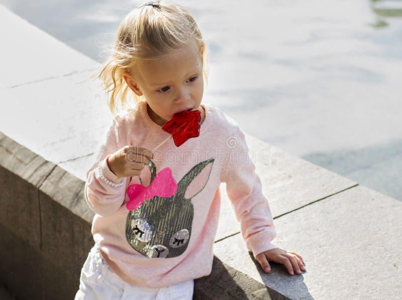 Белокурая девушка есть часть конфеты стоковые изображения