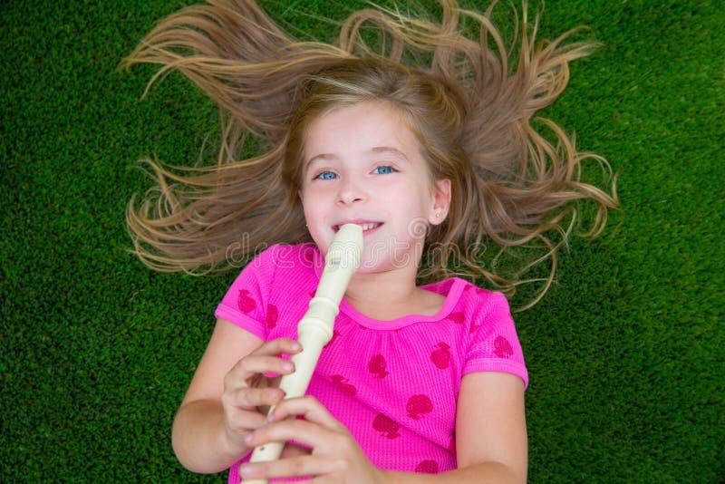 Белокурая девушка детей ребенк играя каннелюру лежа на траве стоковое изображение