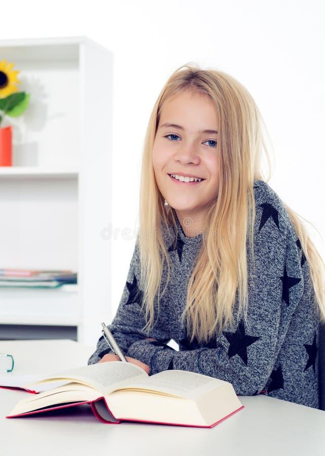 Белокурая девушка делая домашнюю работу стоковое фото