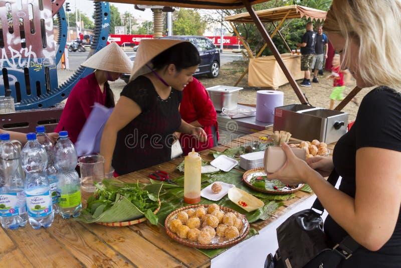 Белокурая девушка покупая азиатскую еду на популярном перекрестном фестивале в Праге, зоне еды варенья еды улицы Holesovice стоковая фотография