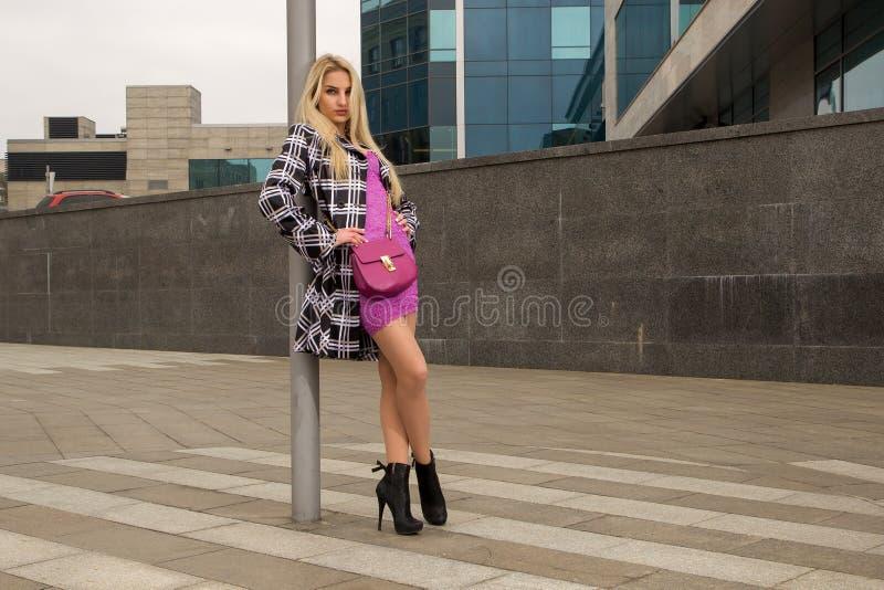 Белокурая девушка представляет в городе стоковые фотографии rf