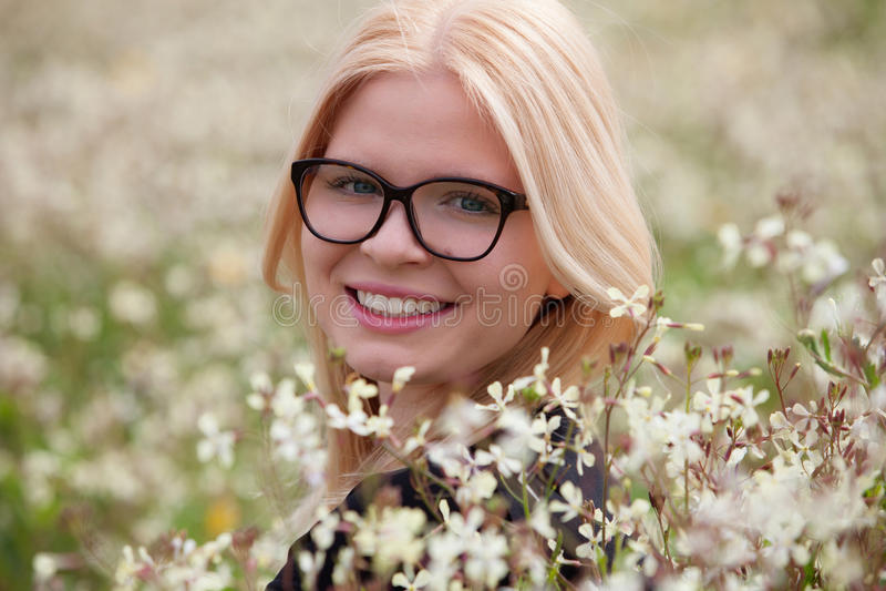 Белокурая девушка при стекла окруженные цветками стоковая фотография rf