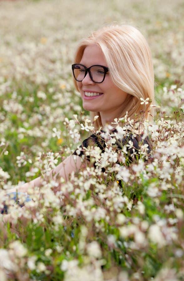 Белокурая девушка при стекла окруженные цветками стоковые изображения
