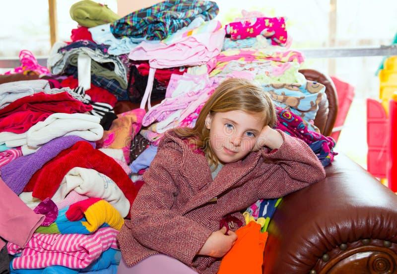 Белокурая девушка ребенк сидя на грязной софе одежд стоковое фото