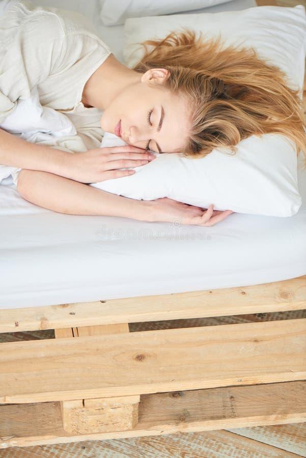 Белокурая девушка спать на белой кровати стоковое фото rf