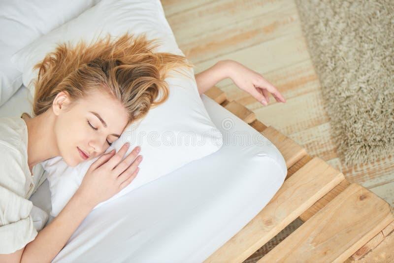 Белокурая девушка спать на белой кровати стоковое изображение