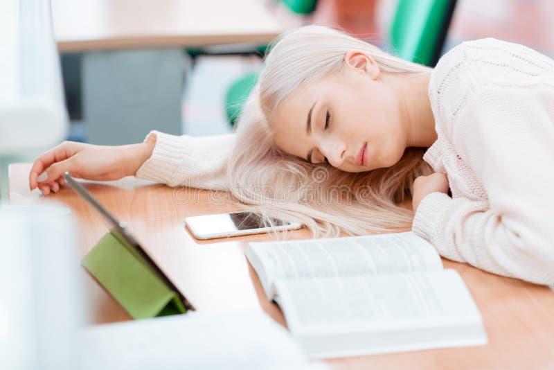 Белокурая девушка спит на столе стоковая фотография rf