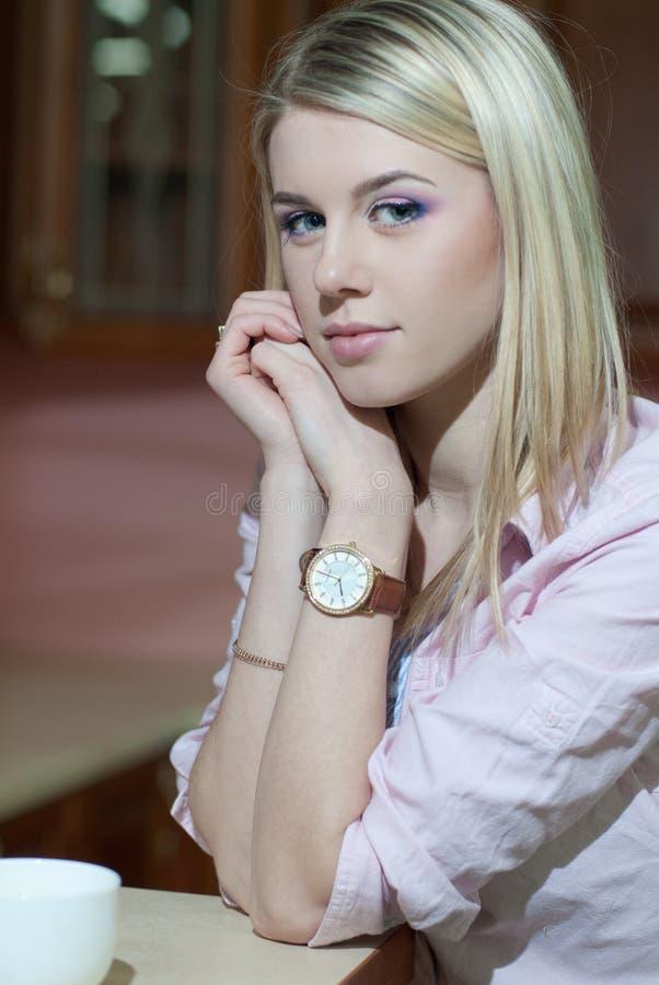 Белокурая девушка с типом волос & чашка на таблице стоковое изображение rf