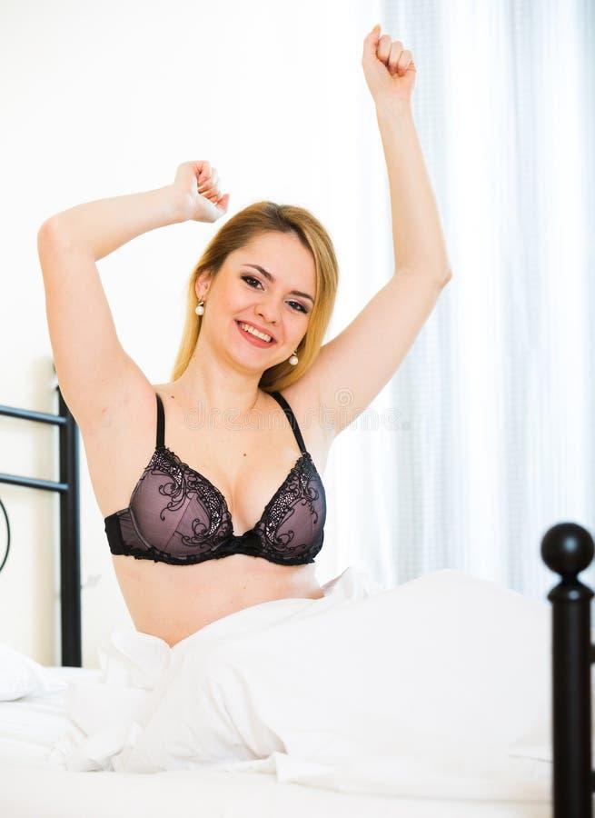 Белокурая девушка stratching в кровати дома стоковое фото rf