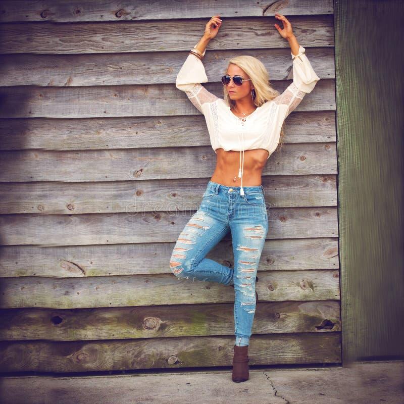 Белокурая женщина в голубых джинсах стоковые изображения