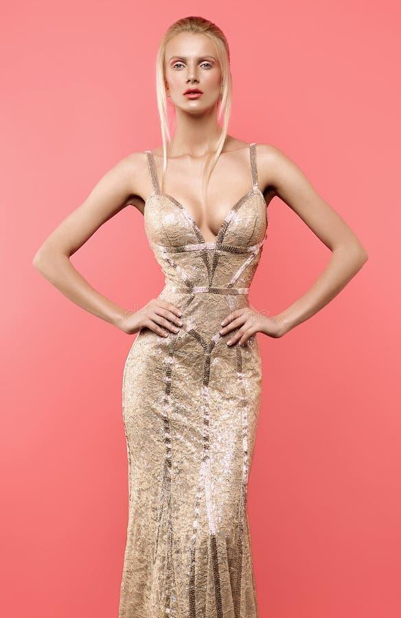 Белокурая женщина в красивом золотом платье стоковые фото