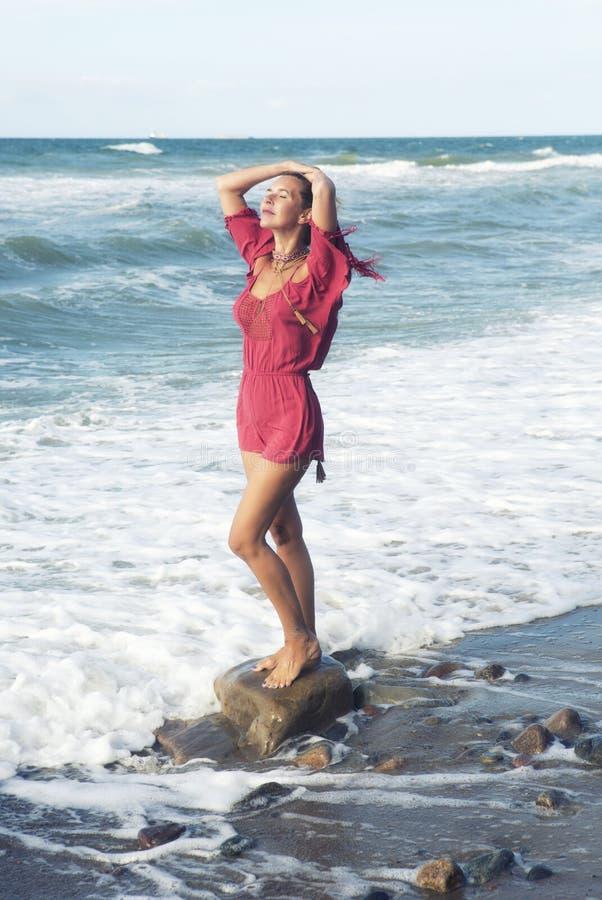 Белокурая женщина в красном платье готовя океан стоковое фото