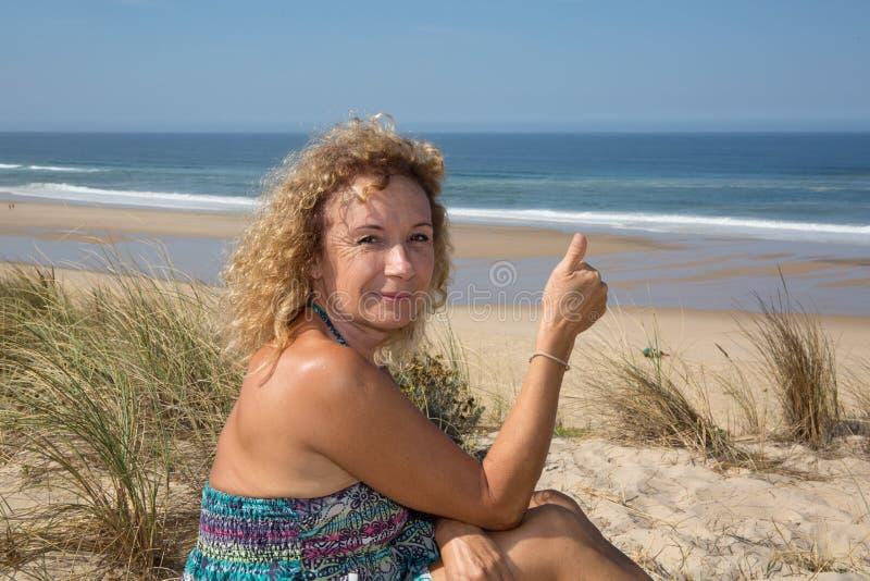 Белокурая женщина в платье показывая большие пальцы руки вверх на пляже стоковое изображение rf