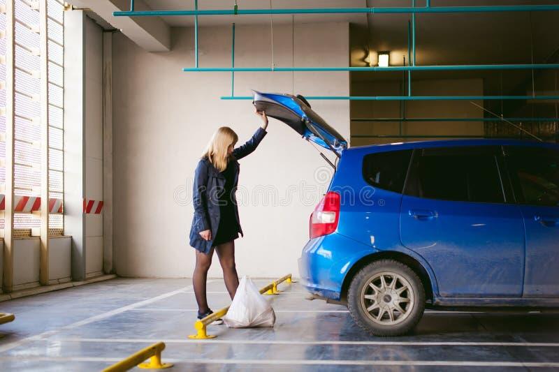 Белокурая женщина в плаще и колготки штабелирует приобретения от гастронома в хоботе цвета автомобиля голубого в крытой парковке  стоковое изображение