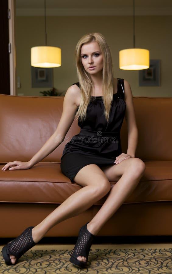 Белокурая женщина в черном платье стоковая фотография rf