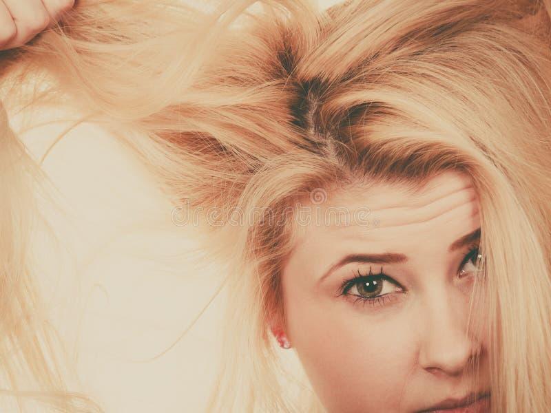 Белокурая женщина держа ее сухие волосы стоковое фото rf