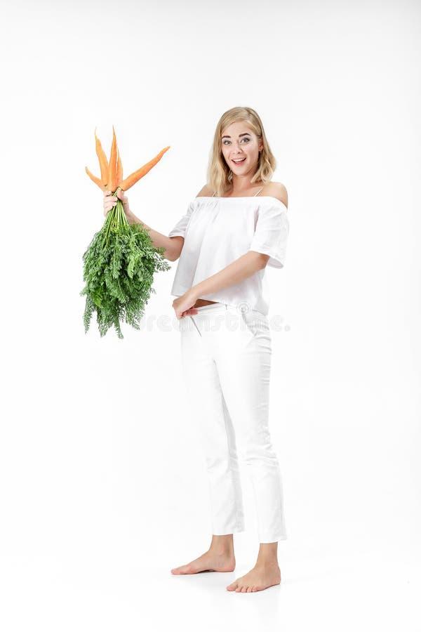 Белокурая женщина держа свежую морковь с зеленым цветом выходит на белую предпосылку девушка ест морковей и растет тонко стоковое изображение rf