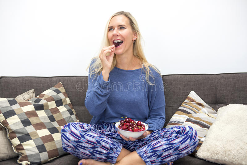 Белокурая женщина есть вишни стоковое фото rf