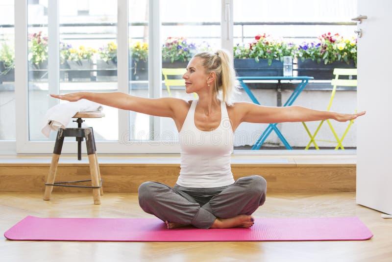 Белокурая женщина делая йогу стоковое изображение rf
