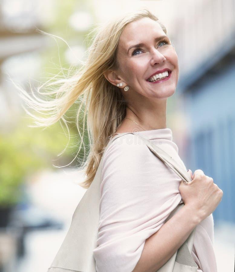 Белокурая женщина идя в улицу стоковое изображение