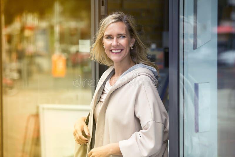 Белокурая женщина идя из магазина стоковое изображение