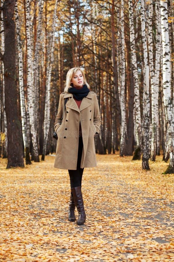 Белокурая женщина моды идя в лес осени стоковая фотография rf