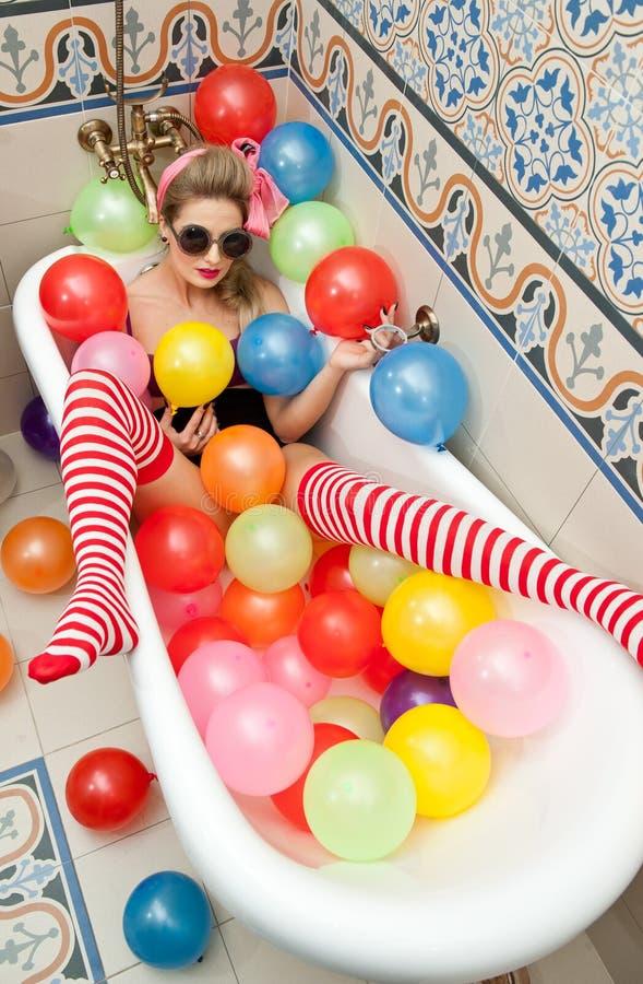 Белокурая женщина при солнечные очки играя в ее трубке ванны с яркими покрашенными воздушными шарами Чувственная девушка с белыми стоковые фото