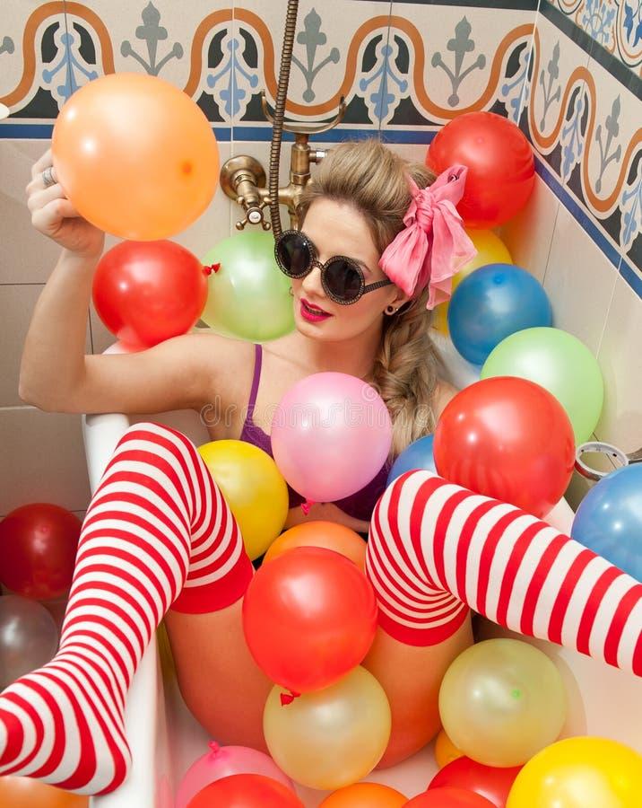 Белокурая женщина при солнечные очки играя в ее трубке ванны с яркими покрашенными воздушными шарами Чувственная девушка с белыми стоковое изображение rf