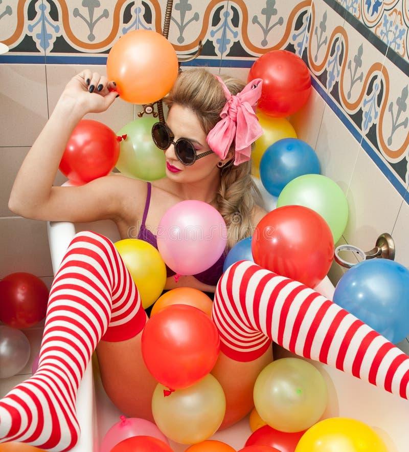 Белокурая женщина при солнечные очки играя в ее трубке ванны с яркими покрашенными воздушными шарами Чувственная девушка с белыми стоковое изображение