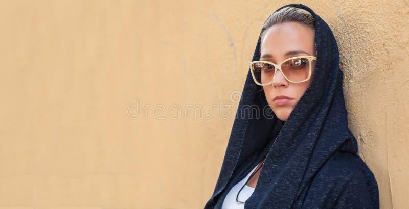 Белокурая женщина при солнечные очки представляя на улице стоковые изображения rf