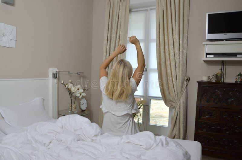 Белокурая женщина протягивая в Bedchamber стоковое фото rf