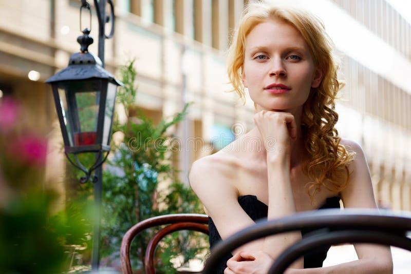 Белокурая женщина сидя в кафе и смотря камеру стоковое изображение