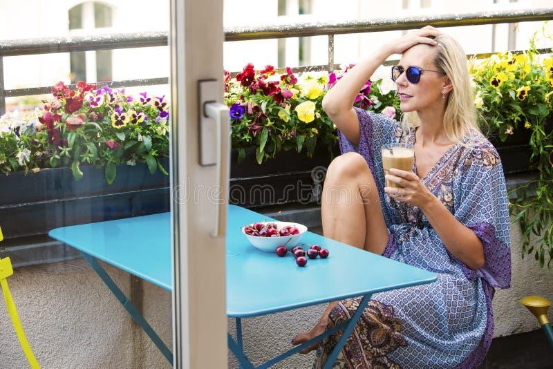 Белокурая женщина сидя на балконе с кофе и вишнями стоковая фотография