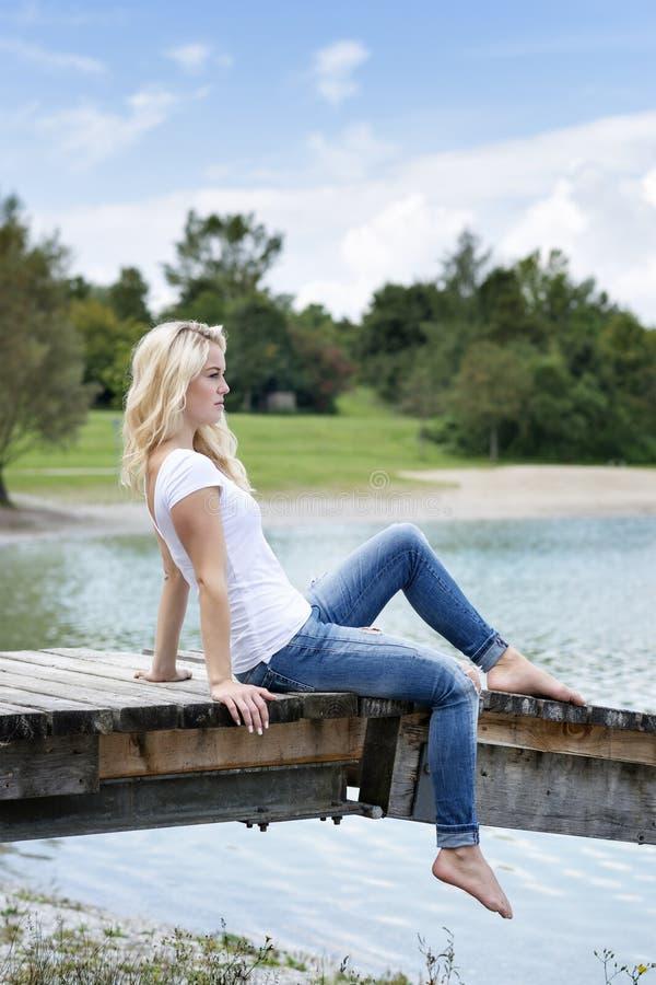 Белокурая женщина сидя на моле стоковое фото rf