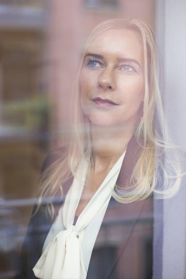 Белокурая женщина смотря из окна стоковые изображения